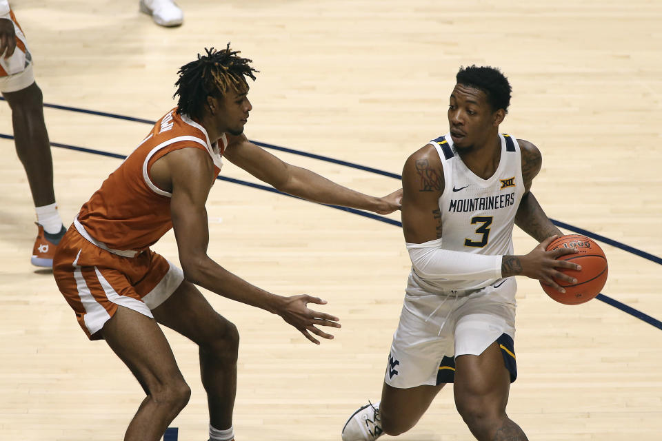 West Virginia forward Gabe Osabuohien (3) passes while defended by Texas forward Greg Brown (4) during the first half of an NCAA college basketball game Saturday, Jan. 9, 2021, in Morgantown, W.Va. (AP Photo/Kathleen Batten)