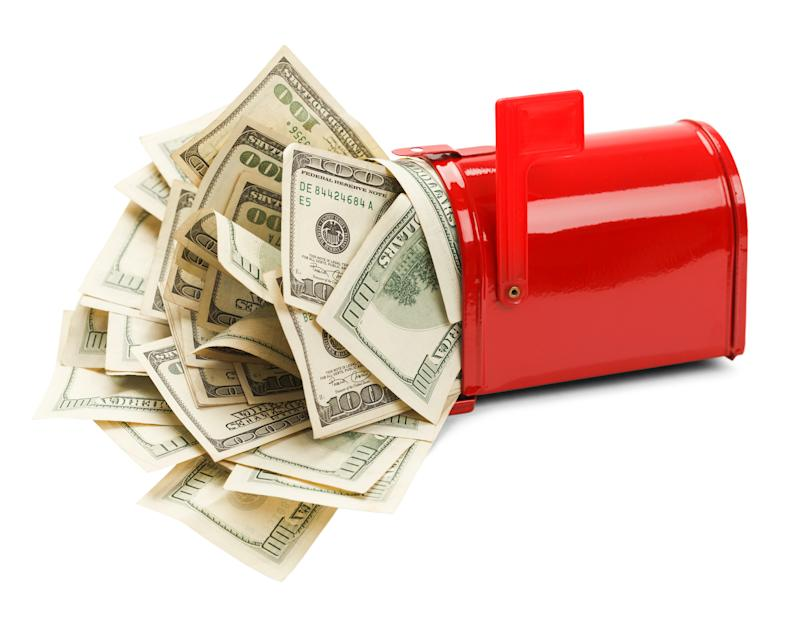 A red mailbox is overflowing with hundred dollar bills that are crammed in it.