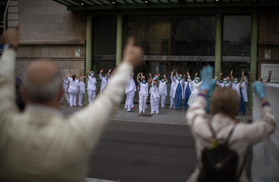 Health workers react as people applaud in the street in support of the medical staff working during the coronavirus outbreak, at the main gate of the Hospital Clinic, on International Nurses Day, Tuesday, May 12, 2020 in Barcelona, Spain. Spain has become the first western Europe to accumulate more than 1 million confirmed infections as the country of 47 million inhabitants struggles to contain a resurgence of the coronavirus. (AP Photo/Emilio Morenatti)