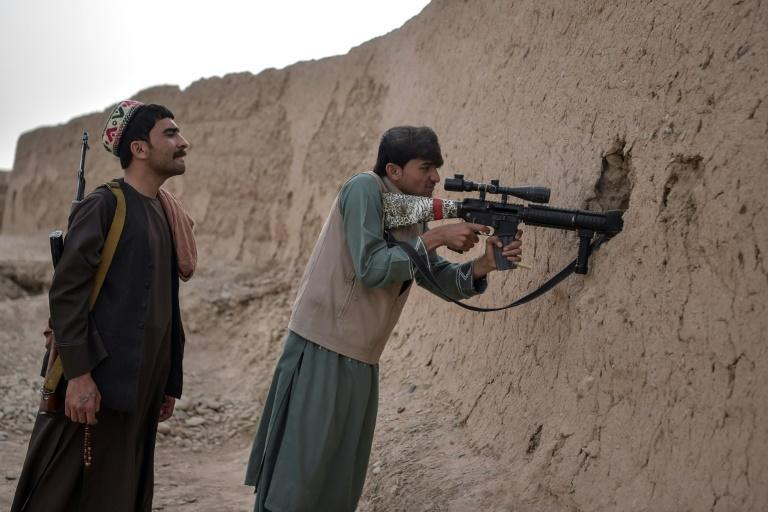 """Members of the Afghan """"Sangorians"""" militia take position during a recent fight with Taliban insurgents in Mukhtar, Helmand Province"""