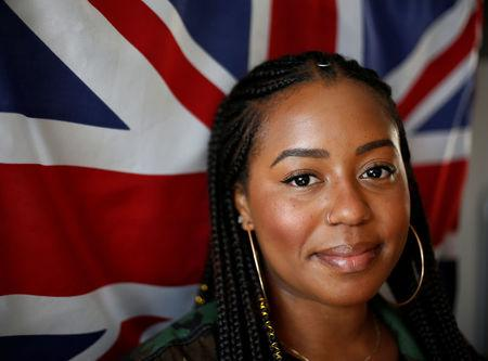 Ishea Brown, who plans to hold a Royal wedding viewing party with 19 of her friends, complete with fascinators and Hennessy, poses for a portrait in front of a UK flag at her apartment in Seattle, Washington, U.S., May 14, 2018. Picture taken May 14, 2018. REUTERS/Lindsey Wasson