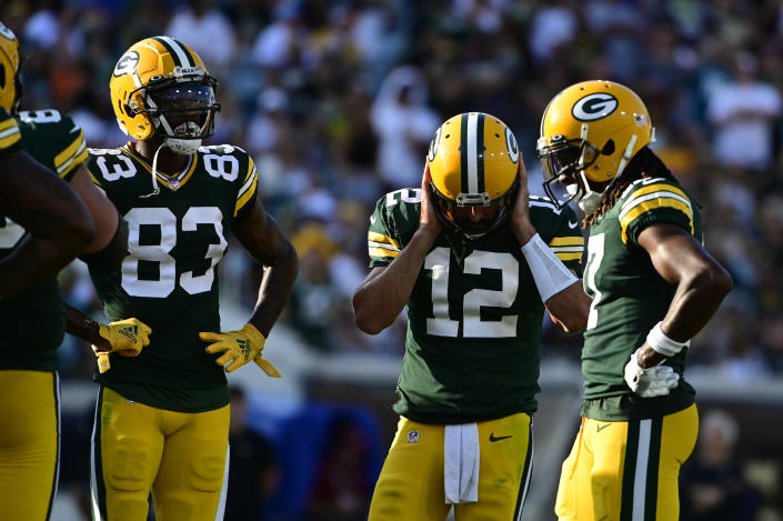Sep 12, 2021; Jacksonville, Florida, USA;  Green Bay Packers quarterback Aaron Rodgers (12) covers his ears in the huddle during the third quarter against the New Orleans Saints at TIAA Bank Field. Mandatory Credit: Tommy Gilligan-USA TODAY Sports