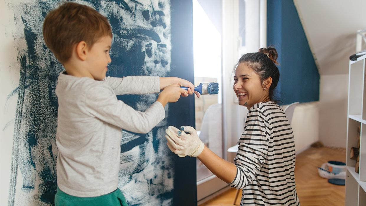 Mother and son working together on repainting a wall in their living room.