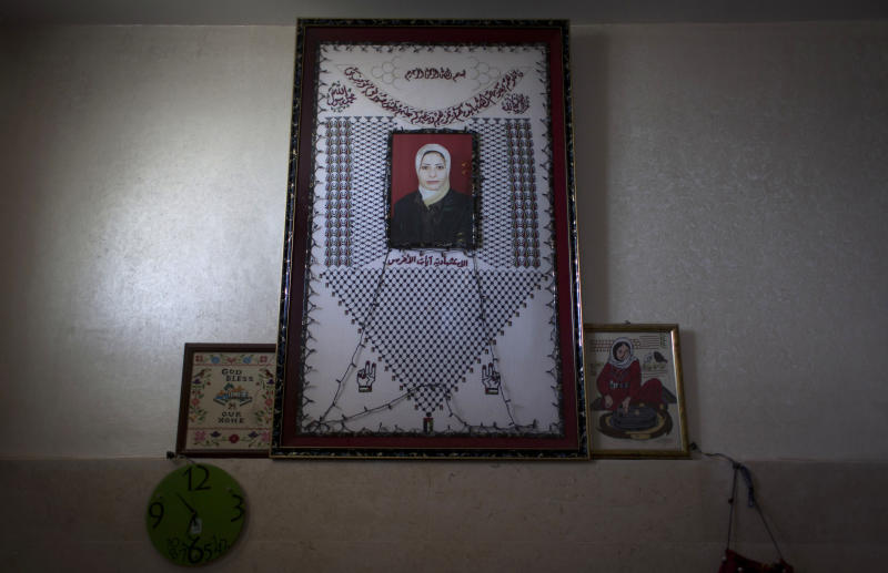 In this photo taken Saturday, Feb. 1, 2014, a photo of late Ayat al-Akhras, who blew herself up in a suicide bombing outside a Jerusalem supermarket in 2002, is seen on a wall at the family house in the West Bank city of Bethlehem. More than a decade later, after appeals from human rights groups, Israel is handing over some 30 bodies of Palestinian assailants, including that of Ayat. (AP Photo/Nasser Nasser)