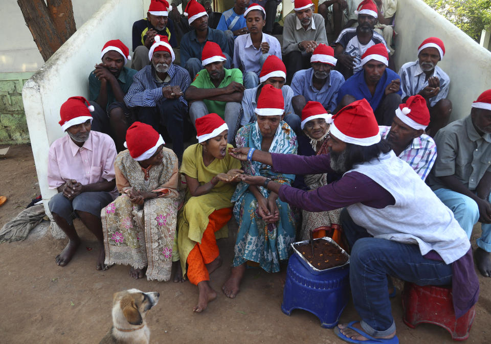 George Rakesh Babu, right, founder of Good Samaritans India, a non-government organization feeds food to a homeless person at a shelter to celebrate Christmas on the outskirts of Hyderabad, India, Friday, Dec. 25, 2020. (AP Photo/Mahesh Kumar A.)