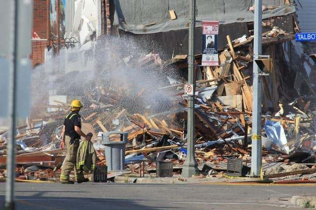 A firefighter stands in front of the rubble left by an explosion in the core of Wheatley on Aug. 26, 2021. (Mike Evans/CBC - image credit)