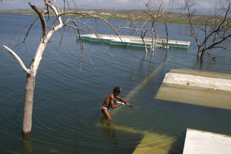 In this Sept. 5, 2012 photo, a man stands on the wall of a submerged home to fish in Lake Azuei near Jimani, Dominican Republic, on the border with Haiti. The waters' rise has worsened exponentially in recent years, especially after heavy rains in 2007 and 2008 hit the island of Hispaniola. Tropical Storm Isaac dumped more water on the region last month, sparking more damage. (AP Photo/Dieu Nalio Chery)