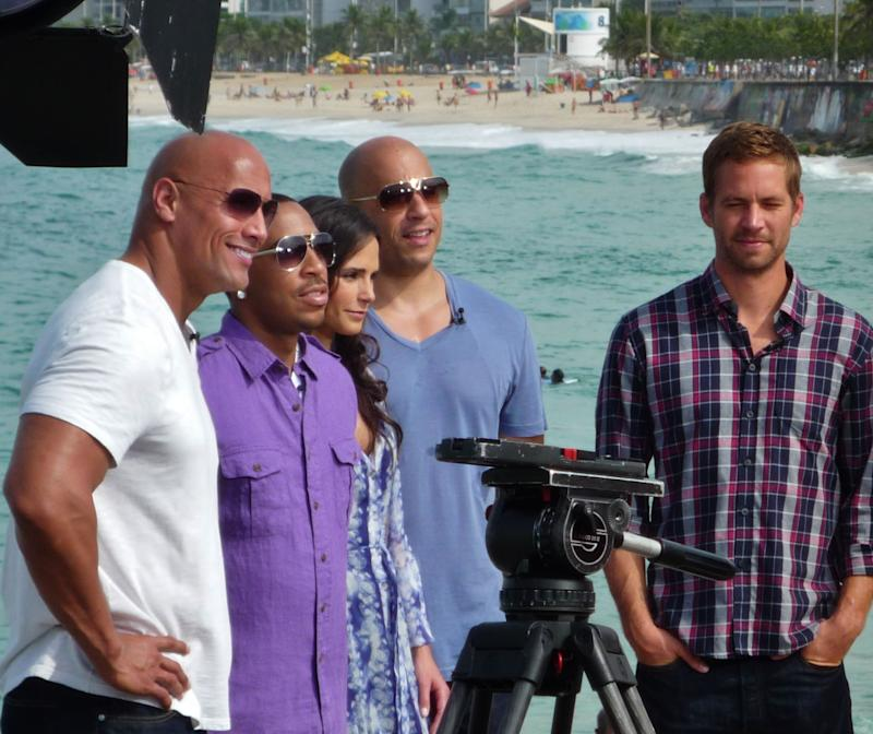 """A picture of Paul Walker and the crew from """"The Fast And The Furious"""" at the beach."""