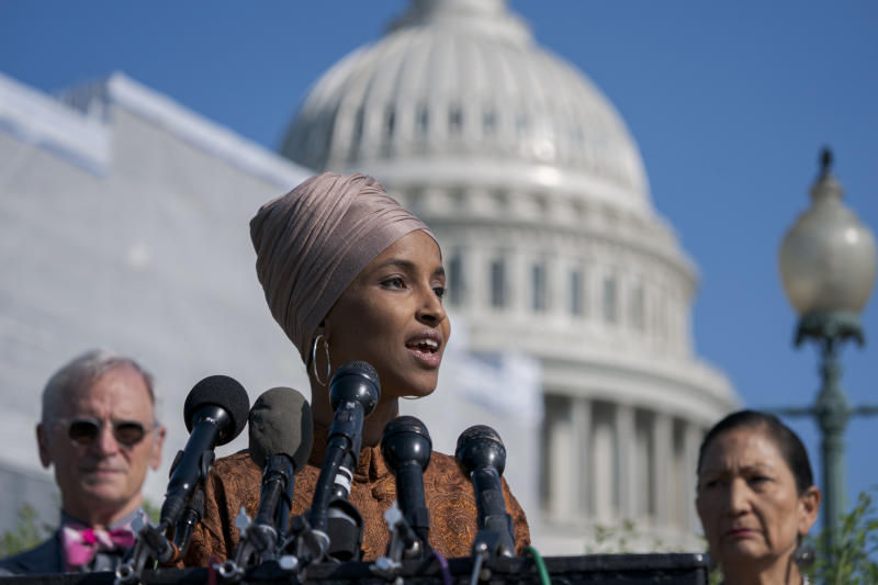 """FILE - In this July 25, 2019 file photo, Rep. Ilhan Omar, D-Minn., center, flanked by Rep. Earl Blumenauer, D-Ore., left, and Rep. Deb Haaland, D-N.M., introduces the Zero Waste Act that would create a federal grant program to help local governments invest in waste reduction initiatives, at the Capitol in Washington. An image circulating on Facebook on Sept. 11 that shows the burning World Trade Center's twin towers with photos of Omar laughing, puts words in the Democratic congresswoman's mouth. Omar, the first Muslim refugee elected to Congress, has faced criticism for using the phrase """"some people did something"""" in remarks about the attacks during a speech in March. (AP Photo/J. Scott Applewhite, File)"""