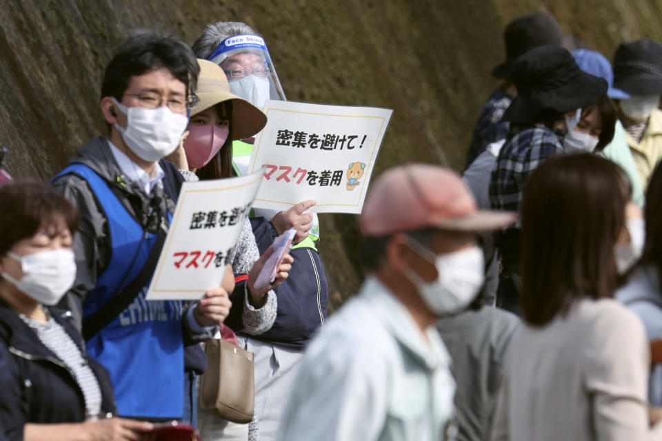 """Organizers hold signs to spectators that read: """"Avoid crowding! Wear masks"""" during the Tokyo Olympic torch relay in Tobe, Ehime prefecture, southwestern Japan, Thursday, April 22, 2021. Tokyo Olympic organizers said Thursday that a Japanese policeman tested positive for COVID-19 a day after his assignment of traffic control at the April 17 leg of the torch relay. It is the first positive test report connected to the relay since it kicked off on March 25. (Kyodo News via AP)"""