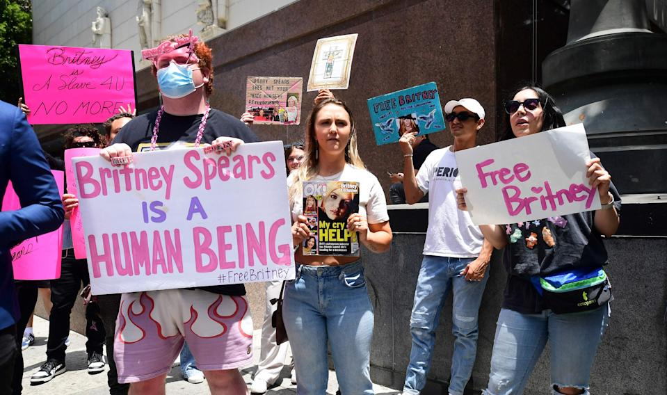 """Fans and supporters hold """"Free Britney"""" signs as they gather outside the County Courthouse in Los Angeles, California on June 23, 2021, during a scheduled hearing in Britney Spears' conservatorship case."""