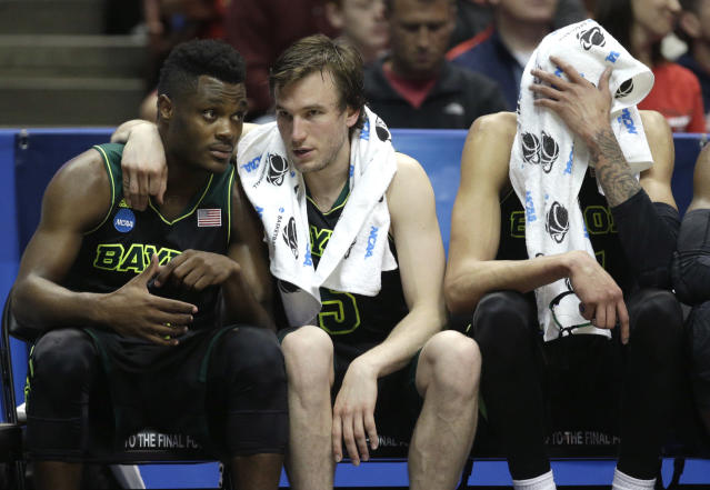 Baylor guard Brady Heslip, center, hugs a teammate as Isaiah Austin wipes his face with towel during the second half against Wisconsin in an NCAA men's college basketball tournament regional semifinal, Thursday, March 27, 2014, in Anaheim, Calif. Wisconsin won 69-52. (AP Photo/Jae C. Hong)