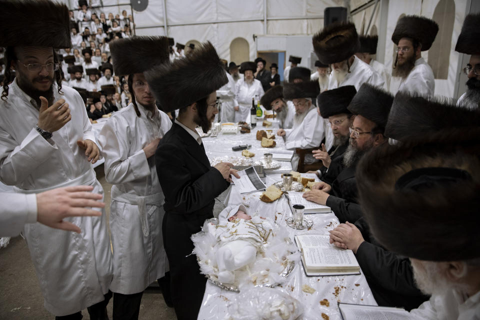 """Yaakov Tabersky, right, presented his firstborn son, Yossef on a silver platter to Jewish priests from the Lelov Hassidic dynasty, during the """"Pidyon Haben"""" ceremony in Beit Shemesh, Israel, Thursday, Sept. 16, 2021. The Pidyon Haben, or redemption of the firstborn son, is a Jewish ceremony hearkening back to the biblical exodus from Egypt. (AP Photo/Oded Balilty)"""