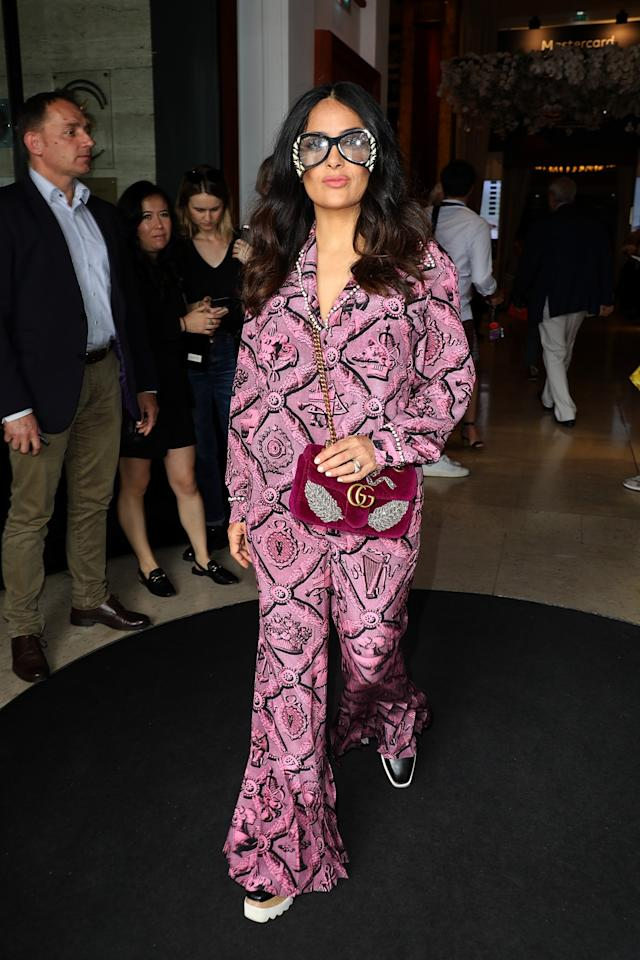 <p>Salma Hayek, whose husband is also Kering's CEO, François-Henri Pinault— is on her way to the Kering Women in Motion lunch sporting a Gucci pajama set lined with pearls, paired with a furry magenta Gucci bag slung across her body and cheeky, oversized sunglasses to match. (Photo: Getty) </p>