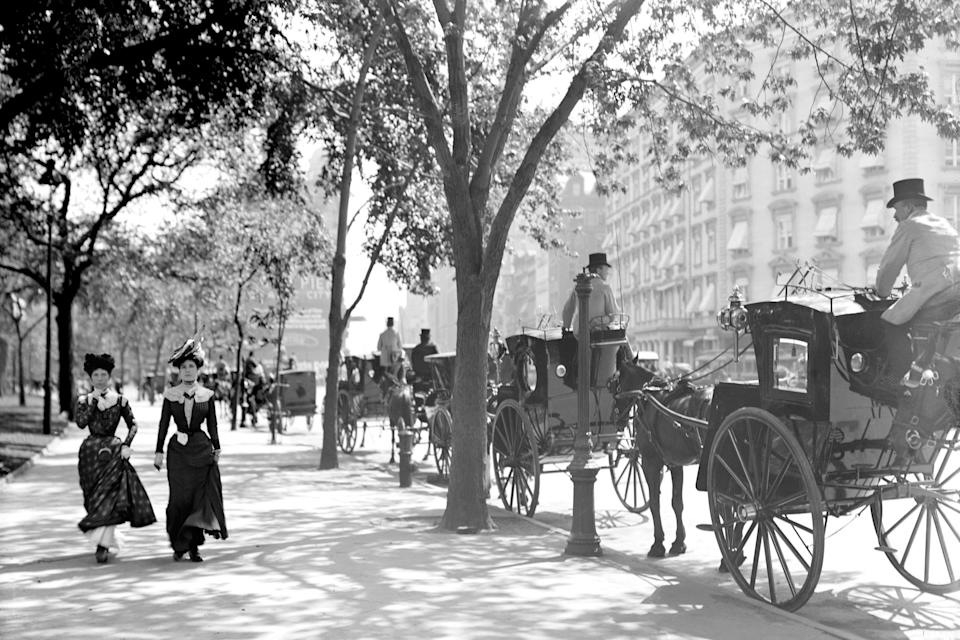 Two women stroll by a line of horse-drawn carriages (then, the equivalent of taxicabs) near Madison Square.
