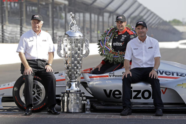 FILE - In this May 28, 2018, file photo, Indianapolis 500 champion Will Power, of Australia, poses with Roger Penske, left, and Tim Cindric, right, with the Borg-Warner Trophy during the traditional winners photo session on the start/finish line at the Indianapolis Motor Speedway in Indianapolis. Indianapolis Motor Speedway and the IndyCar Series were sold to Penske Entertainment Corp. in a stunning move Monday, Nov. 4, 2019, that relinquishes control of the iconic speedway from the Hulman family after 74 years. (AP Photo/Darron Cummings, File)