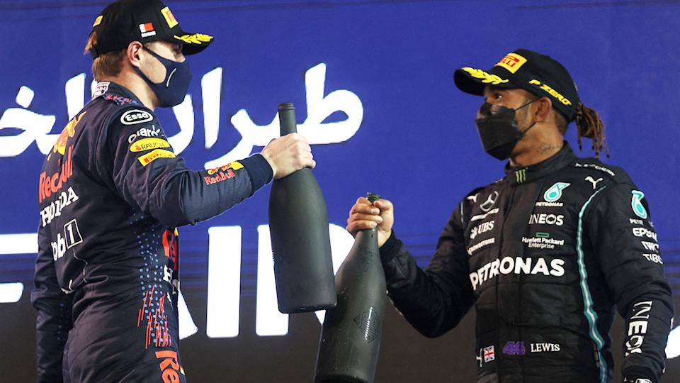 Red Bull's Max Verstappen and Mercedes' Lewis Hamilton celebrate on the podium after the Bahrain GP.  (Photo by LARS BARON/AFP via Getty Images)