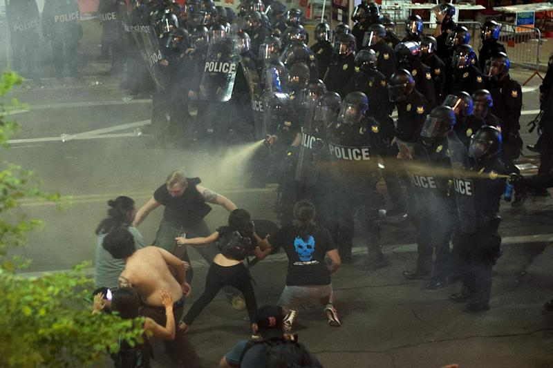 Reeling: Protesters recoil after being pepper-sprayed by police in Phoenix