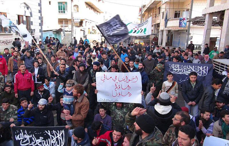 """This citizen journalism image taken on Friday, Jan. 25, 2013 and provided by Edlib News Network, ENN, which has been authenticated based on its contents and other AP reporting, shows Syrians chanting slogans and holding a poster in Arabic that reads, """"Our brothers in Mali, your blood is our blood,"""" as well as Islamic banners during a demonstration after Friday prayer, in Binnish village, Idlib province, north Syria. (AP Photo/Edlib News Network ENN)"""
