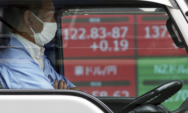 A driver waits in front of an electronic stock board of a securities firm in Tokyo, Tuesday, June 11, 2019. Asian shares are mostly higher as investor jitters over trade eased after U.S. President Donald Trump suspended plans to impose tariffs on Mexican imports and said he expects to meet with the Chinese leader. (AP Photo/Koji Sasahara)