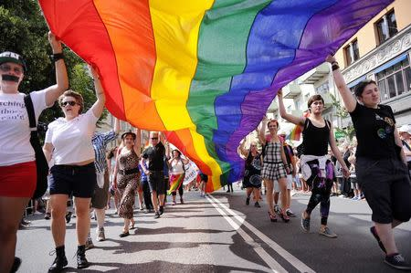Participants carrying a rainbow flag attend the annual gay pride parade in Stockholm