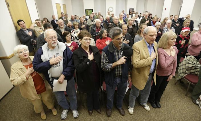 In this Feb. 7, 2013 photo, a group of supporters of Rep. Jason Chaffetz hold their hands over their hearts during the flag salute at a town hall meeting in Heber City, Utah. Chaffetz flew home from Washington last week to attend the town hall meeting. Many voters here and in similar communities elsewhere still want to do whatever it takes to stop President Obama, and the politicians they elect are listening. (AP Photo/Rick Bowmer)