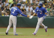 Toronto Blue Jays' Edwin Encarnacion, right, is congratulated by third base coach Luis Rivera (2) after hitting a home run off Oakland Athletics Kendall Graveman in the second inning of a baseball game Tuesday, July 21, 2015, in Oakland, Calif. (AP Photo/Ben Margot)