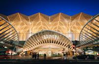 "The second station designed by Santiago Calatrava on this list, <a href=""https://www.cntraveler.com/destinations/lisbon?mbid=synd_yahoo_rss"" rel=""nofollow noopener"" target=""_blank"" data-ylk=""slk:Lisbon's"" class=""link rapid-noclick-resp"">Lisbon's</a> modernist Gare do Oriente is made up of Gothic-inspired concrete arches and an intricate lattice of steel and glass ""trees,"" <a href=""https://www.calatrava.com/projects/oriente-station-lisboa.html"" rel=""nofollow noopener"" target=""_blank"" data-ylk=""slk:as the architect describes them"" class=""link rapid-noclick-resp"">as the architect describes them</a>. While the bright white station is a marvel in the daytime, it is at its finest at night, when the geometric forest is lit up from below. Besides serving as a prime example of Calatrava's work, the beautiful train station functions as a bus terminal and hub for high-speed, regional, and commuter trains."