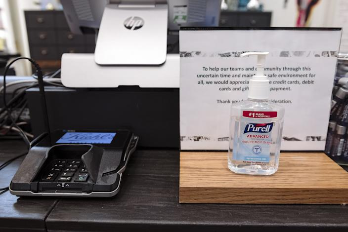 A bottle of hand sanitizer sits next to a credit card machine at a Kiehl's store at Westfield San Francisco Centre in San Francisco, California, U.S., on Thursday, June 18, 2020. (Michael Short/Bloomberg via Getty Images)