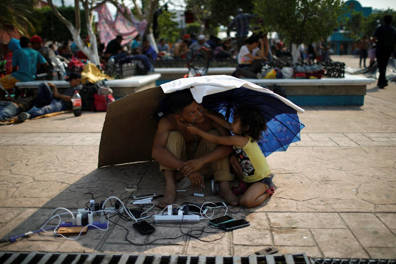 A migrant from Honduras watch other migrants' cellphones as they gather in an improvised shelter during a break in their journey towards the United States, in Escuintla, Mexico April 19, 2019. REUTERS/Jose Cabezas     TPX IMAGES OF THE DAY