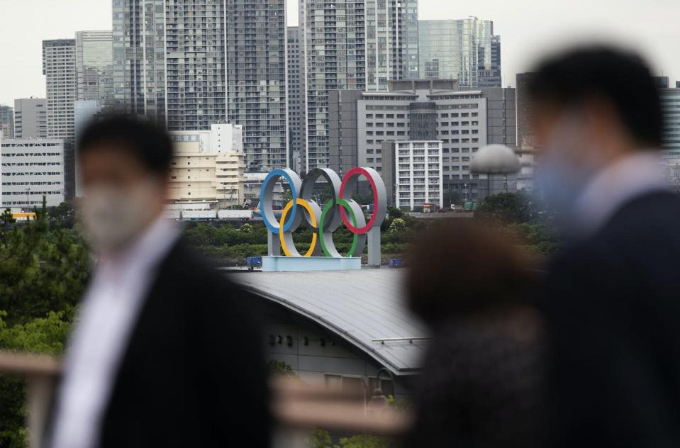 """<span class=""""caption"""">The statue of the Olympics rings overlooks people visiting a nearby shopping mall in Tokyo. </span> <span class=""""attribution""""><span class=""""source"""">(AP Photo/Hiro Komae) </span></span>"""