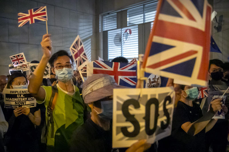 Demonstrators wave British flags during a rally outside of the British Consulate in Hong Kong, Wednesday, Oct. 23, 2019.  Some hundreds of Hong Kong pro-democracy demonstrators have formed a human chain at the British consulate to rally support for their cause from the city's former colonial ruler. (AP Photo/Mark Schiefelbein)