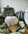 """<p>Who needs orange?! Tame down the classic Halloween color combo by focusing on black and white. These painted mudcloth-inspired pumpkins prove that a simple color palette can still pack a punch.</p><p><strong>Get the tutorial at <a href=""""https://www.houseonlongwoodlane.com/home-renovation/diy-mud-cloth-pumpkins-fall-tablescape/"""" rel=""""nofollow noopener"""" target=""""_blank"""" data-ylk=""""slk:House on Longwood Lane"""" class=""""link rapid-noclick-resp"""">House on Longwood Lane</a>.</strong></p><p><strong><a class=""""link rapid-noclick-resp"""" href=""""https://www.amazon.com/Paint-Painting-Ceramic-Acrylic-Markers/dp/B07485T22B/ref=sr_1_5?tag=syn-yahoo-20&ascsubtag=%5Bartid%7C10050.g.3739%5Bsrc%7Cyahoo-us"""" rel=""""nofollow noopener"""" target=""""_blank"""" data-ylk=""""slk:SHOP PAINT PENS"""">SHOP PAINT PENS</a></strong></p>"""