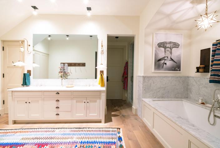 More custom woodwork is found in the primary bathroom, this time in the form of towel hooks and wall shelves. There are also Dusen Dusen towels from Coming Soon NY, a star-shaped light fixture from Vaughan, and another Carol Piper rug.