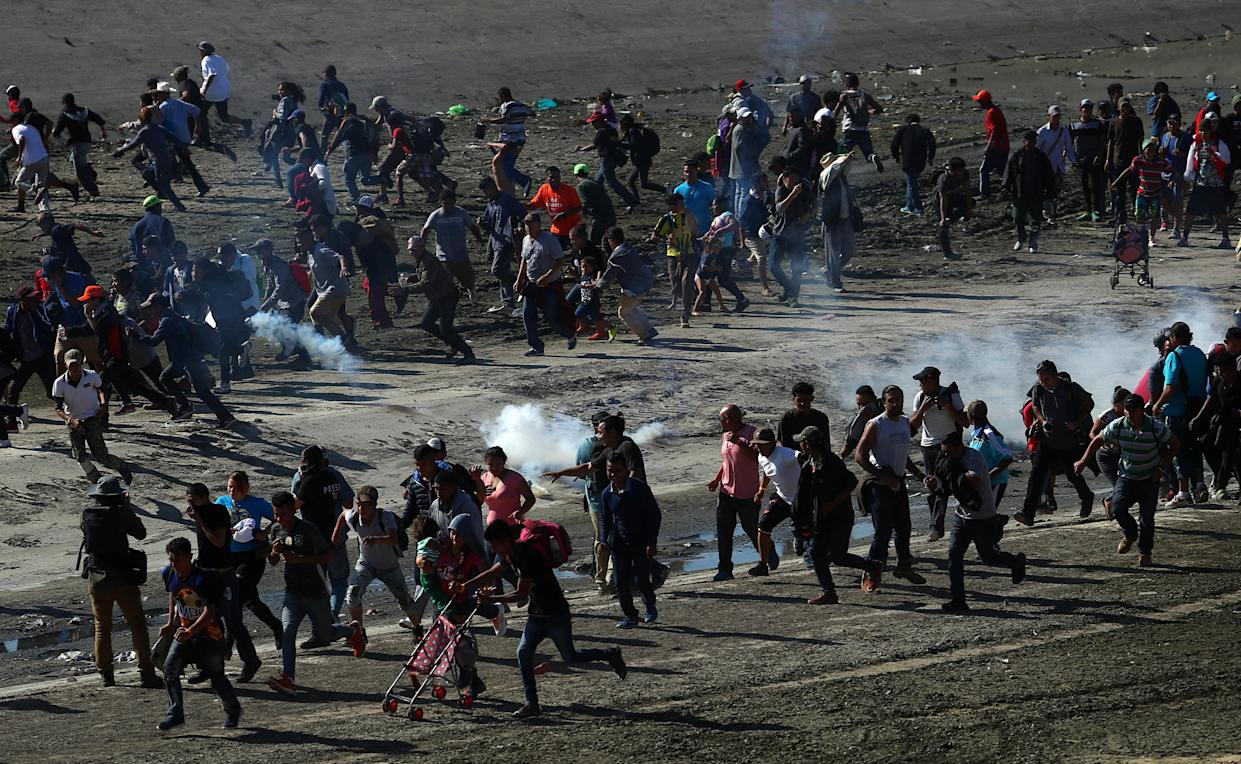 Migrants, part of a caravan of thousands from Central America trying to reach the United States, run from tear gas released by U.S border patrol, near the border fence between Mexico and the United States in Tijuana, Mexico, November 25, 2018. (Photo: Hannah McKay/Reuters)