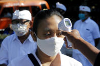 A security person checks the body temperature of a worshipper at a temple amid new coronavirus outbreak in Bali, Indonesia Saturday, July 4, 2020. (AP Photo/Firdia Lisnawati)