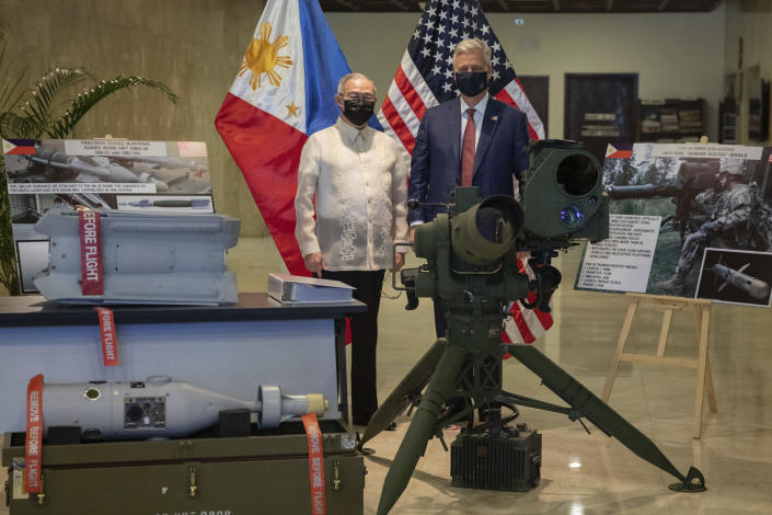 U.S. National Security Advisor Robert Robert O'Brien, right, and Philippines' Secretary of Foreign Affairs Teodoro Locsin Jr. pose in between precision-guided ammunitions and other defense articles during a turnover ceremony at the Department of Foreign Affairs in Pasay City, Philippines Monday, Nov. 23, 2020. (Eloisa Lopez/Pool Photo via AP)