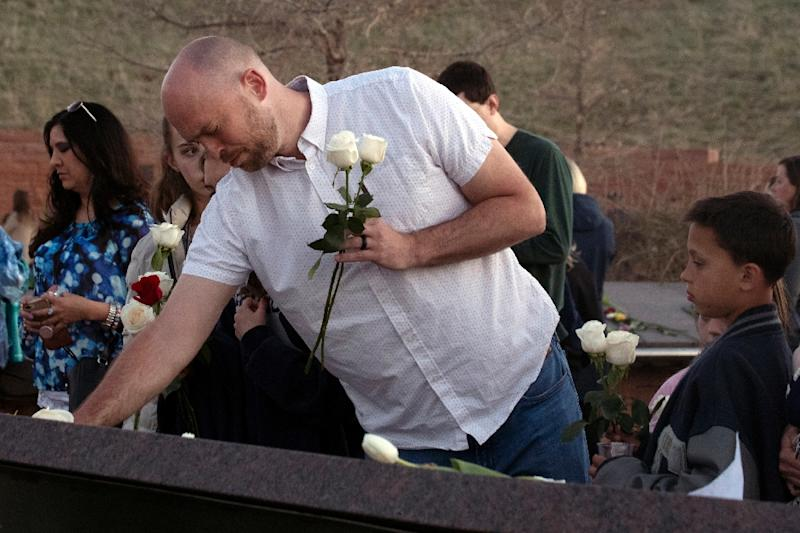 Will Beck, a Columbine High School massacre survivor, places flowers during a vigil in Littleton, Colorado to the 1999 shooting (AFP Photo/Jason Connolly)