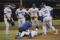Los Angeles Dodgers medical staff Yosuke Nakajima, bottom left, attends to relief pitcher Dustin May, front, after May was hit by a batted ball from Arizona Diamondbacks' Jake Lamb during the fourth inning of a baseball game Sunday, Sept. 1, 2019, in Phoenix. Dodgers' David Freese, left, Justin Turner (10), Chris Taylor (3), Dave Roberts (30) and Jedd Gyorko, right, all look on. (AP Photo/Ross D. Franklin)