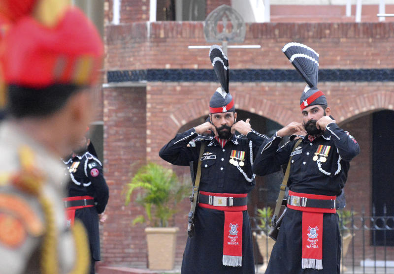Pakistan Rangers soldiers face Indian Border Security Force soldiers at a daily closing ceremony on the Indian side of the Attari-Wagah border, Friday, Aug. 9, 2019. About 8,000 supporters of a Pakistani Islamist party are marching toward the Indian embassy in Islamabad to denounce New Delhi's actions to change the special status of the disputed Himalayan region of Kashmir. Both Pakistan and India claim all of Kashmir. Tensions have soared this week after India downgraded the Muslim-majority region's status from statehood to a territory. (AP Photo/Prabhjot Gill)