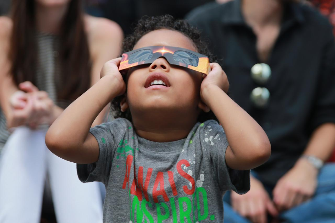 <p>John Deacon checks out the total solar eclipse wearing eclipse glasses in Union Square in New York City on Aug. 21, 2017. (Gordon Donovan/Yahoo News) </p>