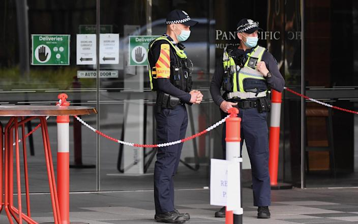 Police stand guard at a hotel in Melbourne - Getty