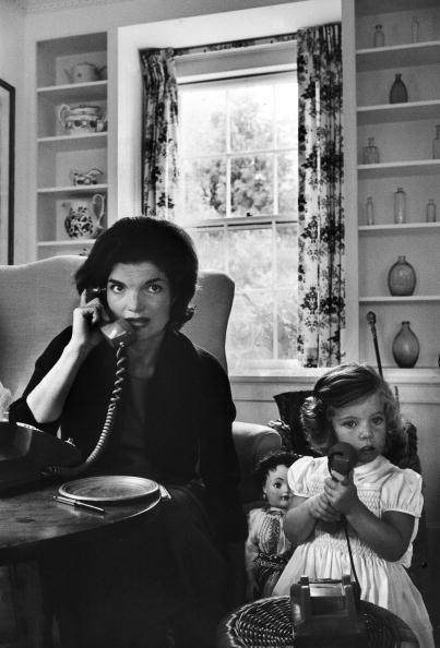 <p>Jackie Kennedy takes a phone call, while daughter Caroline plays with a phone of her own. </p>