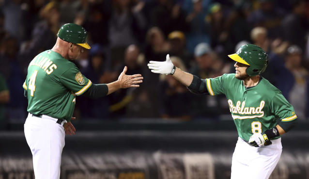 Oakland Athletics' Jed Lowrie, right, is congratulated by third base coach Matt Williams after hitting a home run against the Cleveland Indians during the eighth inning of a baseball game Friday, June 29, 2018, in Oakland, Calif. (AP Photo/Ben Margot)