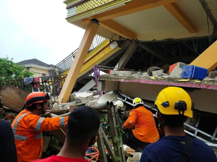 Members of a search and rescue agency team dig through rubble after an earthquake, in Mamuju