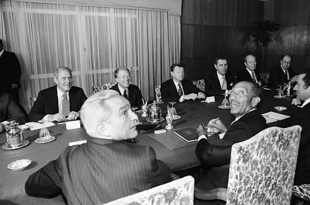 <p>Egypt's President Anwar Sadat and Prime Minister Mustafa Khalil, foreground, look back at the photographers as the U.S. delegation looks on across the table during a meeting in Alexandria Friday, March 9, 1979. The U.S. delegation, from left, Secretary of State Cyrus Vance, President Jimmy Carter, National Security Advisor Zbigniew Brzezinski, Ambassador Hermann Eilts and Ambassador at large Alfred Atherton. (Photo: AP) </p>