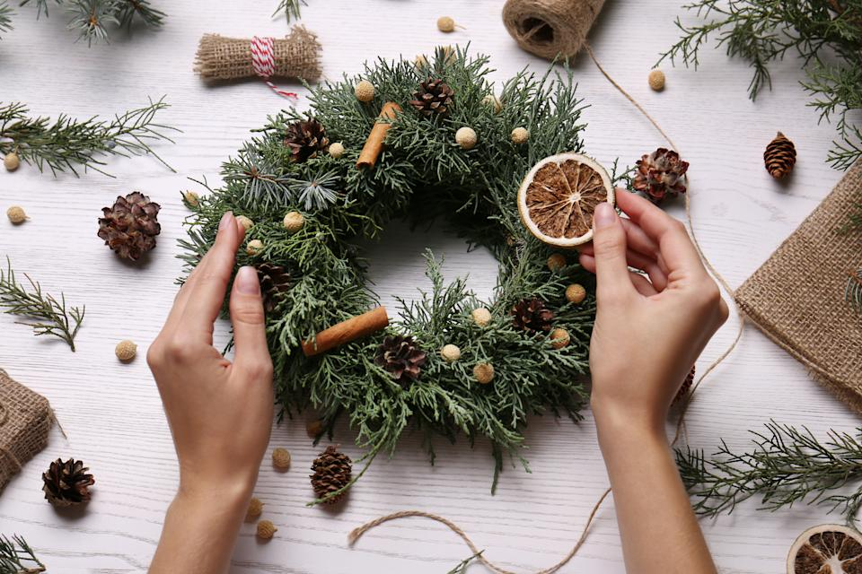 Florist making beautiful Christmas wreath at white wooden table, top view
