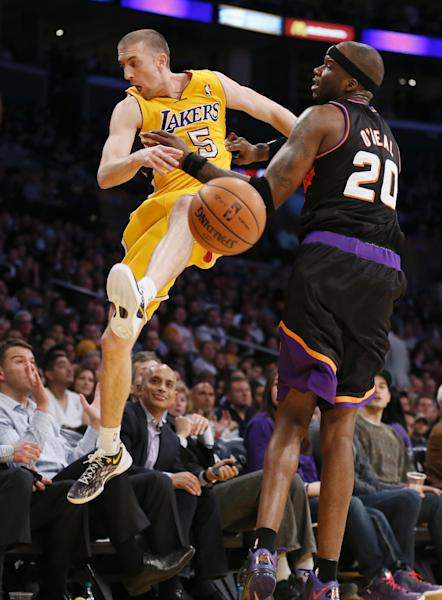 Los Angeles Lakers' Steve Blake, left, tries to save a ball from going out of bounds as Phoenix Suns' Jermaine O'Neal, right, defends during the first half of an NBA basketball game, Tuesday, Feb. 12, 2013, in Los Angeles. (AP Photo/Danny Moloshok)