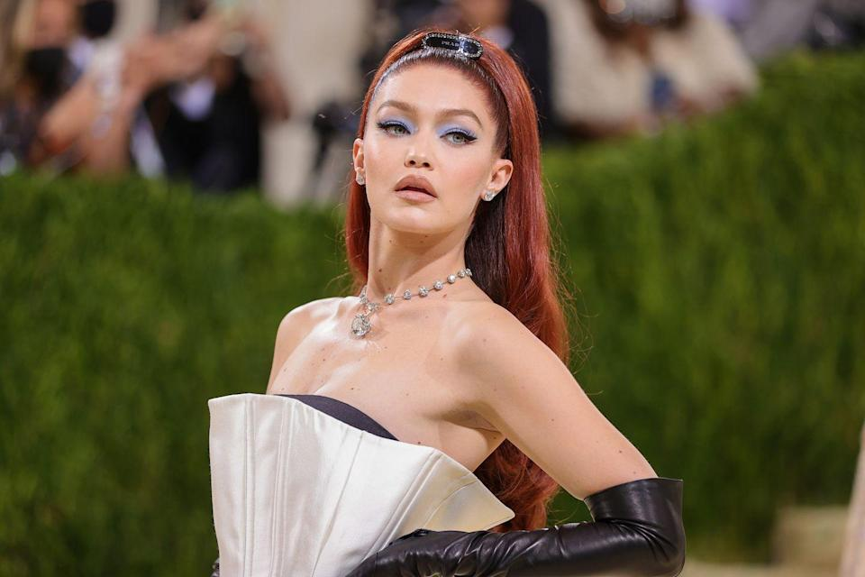 <p>The supermodel debuted Jessica Rabbit-red hair, styled in a retro-inspired ponytail punctuated with a Prada brooch to match her gown. Her make-up, by long-term collaborator Erin Parsons, paired powdery blue shadow with browny-pink lipstick.</p>