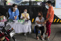 A woman holds the hands of her husband as they wait to be inoculated with China's Sinovac COVID-19 vaccine at a drive-thru vaccination center in Manila, Philippines, Tuesday, June 22, 2021. The Philippine president has threatened to order the arrest of Filipinos who refuse COVID-19 vaccination and told them to leave the country for hard-hit countries like India and the United States if they would not cooperate with massive efforts to end the pandemic. (AP Photo/Aaron Favila)